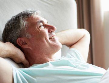 Mann liegt glücklich im Bett