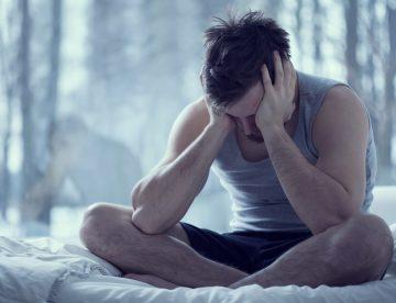 Durchschlafstörungen, Mann sitzt im Bett und kann nicht Schlafen