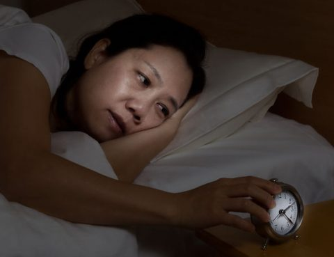 Frau mit Schlafstörungen schaut auf Wecker
