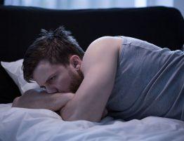 Unruhiger Schlaf - Ursachen und Gefahren - Mann liegt im Bett und denkt nach