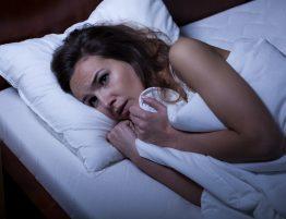 Frau liegt im Bett und kann nicht einschlafen