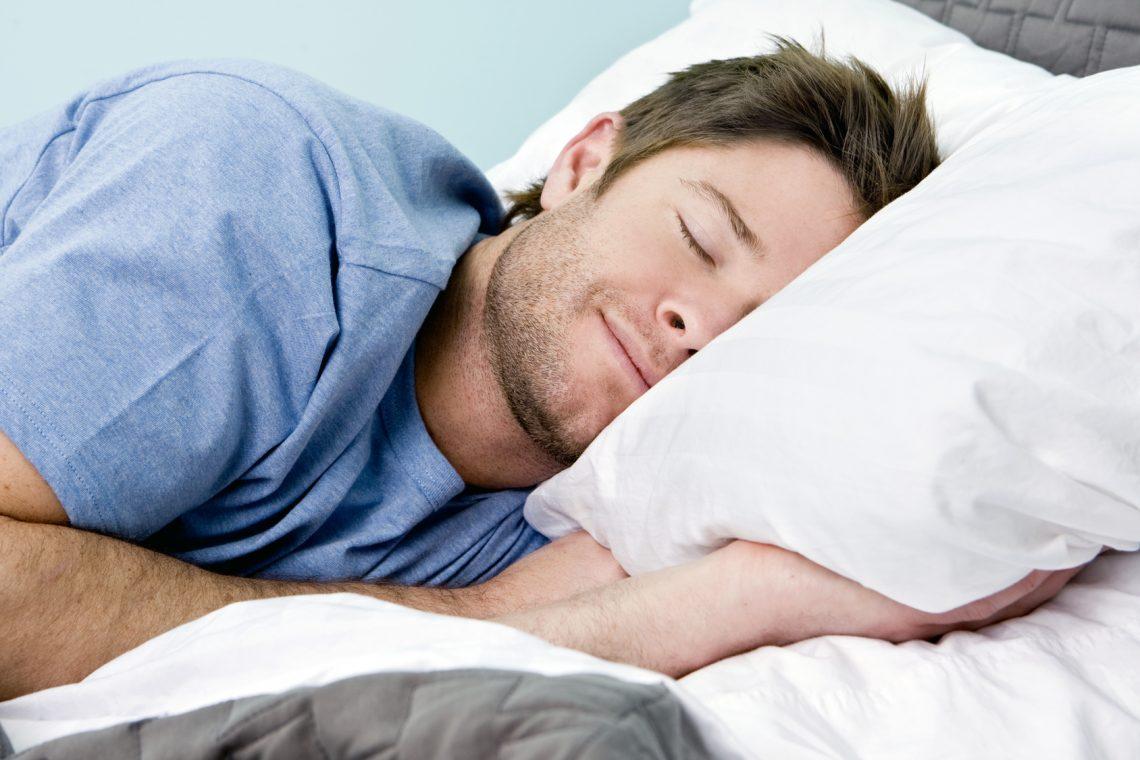 Junger Mann schläft glücklich