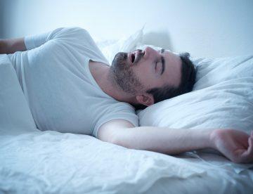 Mann schläft im Bett und schnarcht sehr laut